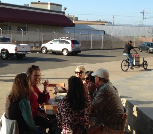 """Kel bikes off with a keg of """"Town"""" while locals enjoy the beer"""